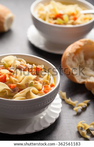 Homemade Turkey Noodle Soup with piping hot rolls on wood
