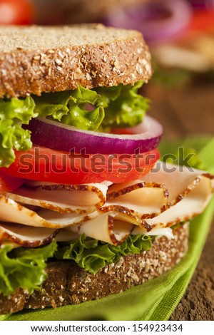 Homemade Turkey Sandwich with Lettuce, Tomato, and Onion - stock photo