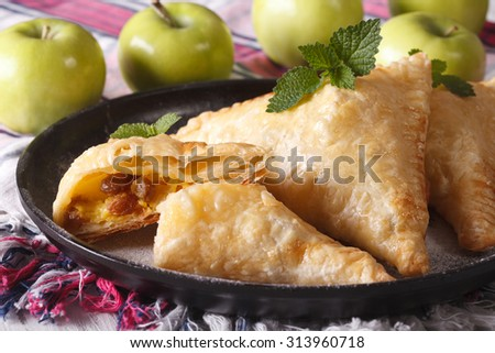 homemade turnover pie with apples and raisins close-up on a plate. horizontal - stock photo