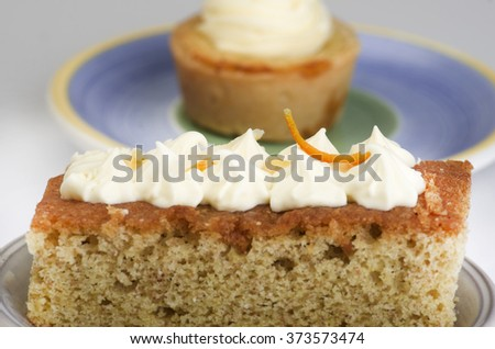 Homemade vanilla cupcake and two pieces of cake with vanilla cream on top on plate.