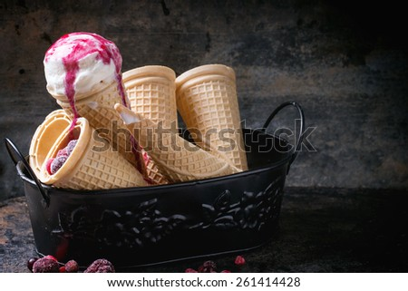 Homemade vanilla ice cream in wafer cones and empty waffer cones, served in metal bowl with frozen berries and spoon over black table. See series - stock photo