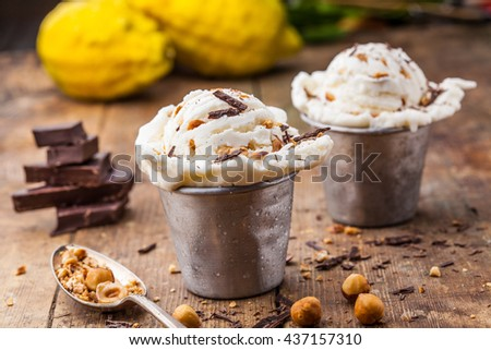Homemade vanilla ice cream with chocolate and hazelnuts, served in tin containers, selective focus - stock photo
