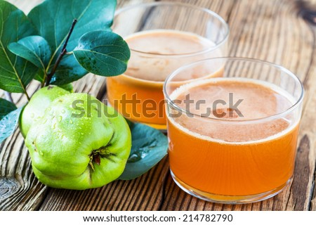 Homemade vegan fruit juice with sweet quince on rustic wooden table - stock photo
