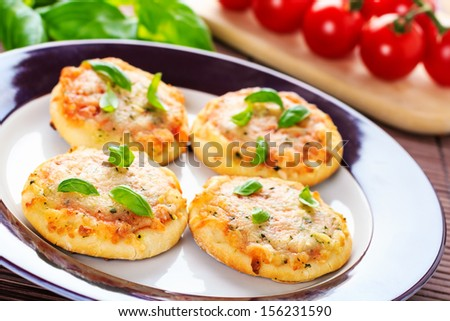 homemade vegetarian mini pizzas served on a wooden board. - stock photo