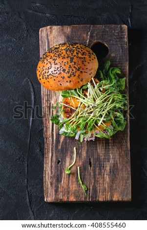 Homemade veggie sweet potato burger with fresh radish and pea sprouts served on wooden chopping board over black textured background. Top view - stock photo