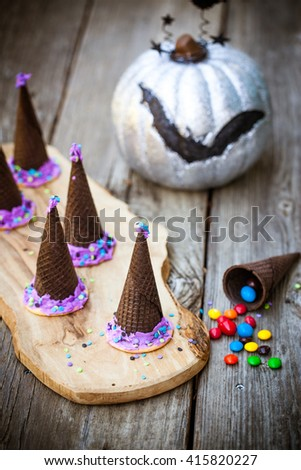 Homemade waffle cones cookies in the form of a Halloween witch hat decorated with purple icing on a wooden background. Selective focus on the hat. Also available in horizontal format.