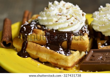 Homemade waffles with chocolate and whipped cream on yellow plate. - stock photo
