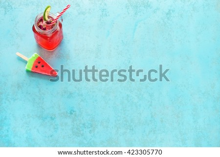 Homemade watermelon lemonade in mason jar with red striped straw and watermelon popsicle on a blue background - stock photo