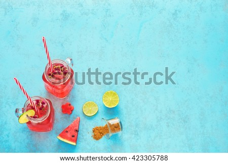 Homemade watermelon lemonade / watermelon cocktail with lime, basil and brown sugar in mason jar with red striped straw. Blue background.  - stock photo