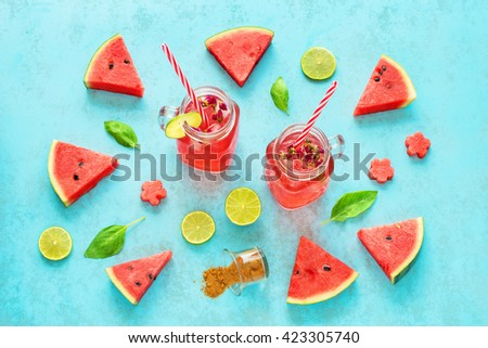 Homemade watermelon lemonade / watermelon cocktail with lime, basil and brown sugar in mason jars with red striped straw. Blue background.  - stock photo