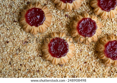 Homemade wheat cookies with berry jam on chopped hazelnuts, selective focus - stock photo