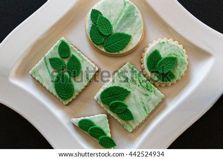 Homemade white butter cookies, decorated with green leaves