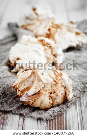Homemade white meringues with brown chocolate stripes - stock photo