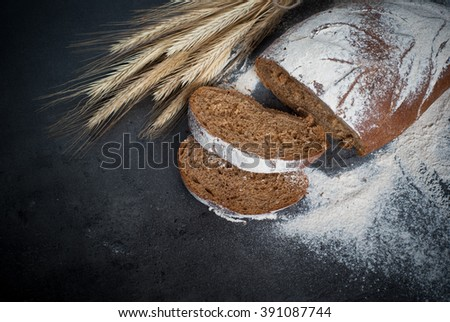 Homemade whole grain bread on a dark background. - stock photo