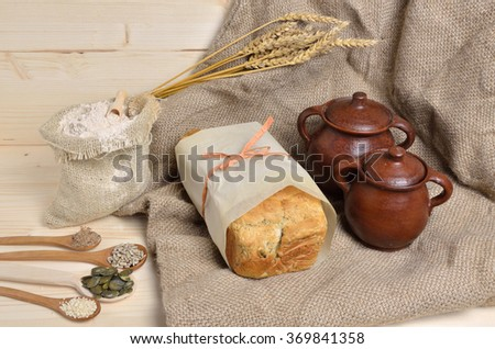 Homemade whole grain bread with pumpkin, flax, sunflower and sesame seeds on jute with sack of whole grain flour and clay pots - stock photo