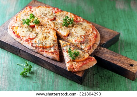 Homemade whole wheat pizza on wooden cutting board, selective focus - stock photo