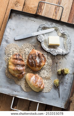 Homemade Yeasted Honey Cornbread Loaves, Butter and Dried Flowers on a Vintage Tray - stock photo