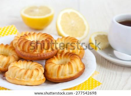 Homemade yellow lemon cakes on white wooden table. Selective focus. - stock photo
