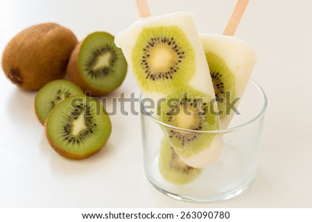 Homemade yogurt ice popsicles with fresh kiwi  for hot summer days on a white table - stock photo