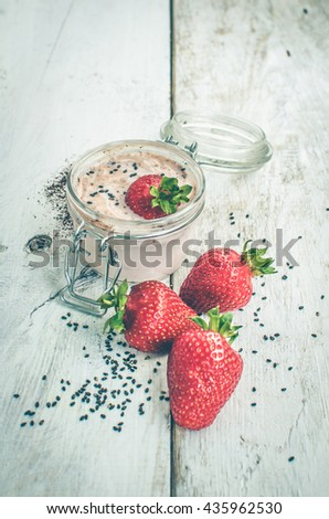 Homemade yogurt in a jar with strawberry, seeds and cacao. Dessert with strawberries on a white wooden background. Fresh strawberry with yogurt. Selective focus. Shallow depth of field. Vertical. - stock photo