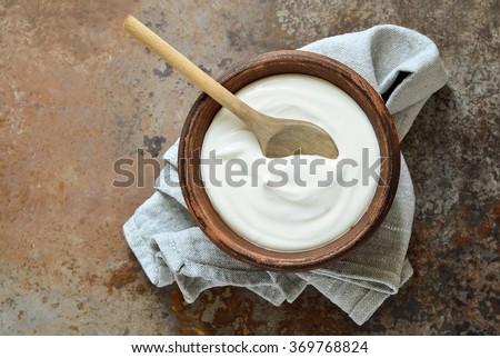 Homemade yogurt or sour cream in a rustic bowl - stock photo