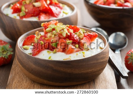 homemade yogurt with fresh strawberries and pistachios in a wooden bowl, close-up, horizontal - stock photo