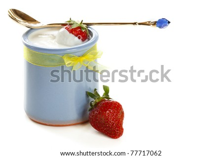 Homemade yogurt with strawberry and golden spoon.