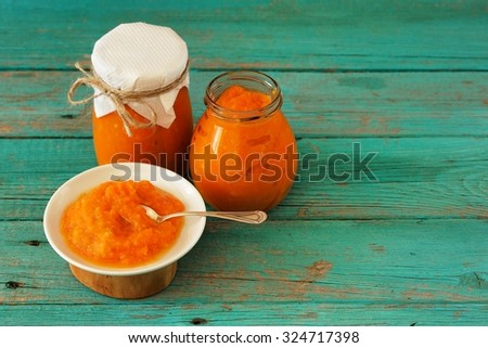 Homemade yummy pumpkin jam in glass jars and in white plate with silver spoon on wooden table copyspace - stock photo