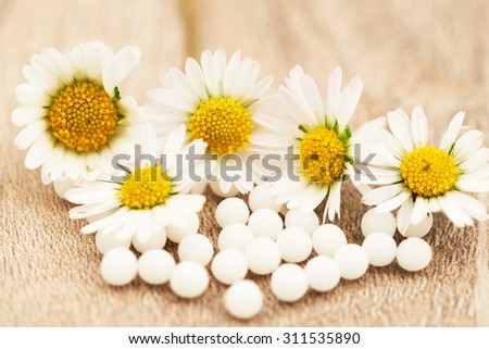 homeopathic granules and daisies, alternative and natural medicine - stock photo