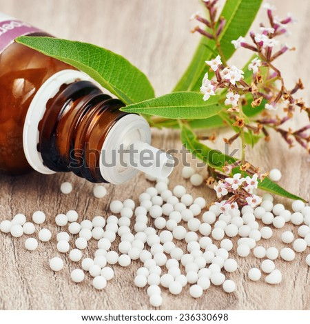 Homeopathic granules scattered around a glass bottle and a medicinal plant on a wooden table. Vertical image with empty space in the bottom for written messages and titles - stock photo