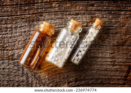 Homeopathic lactose sugar globules and fluid in glass bottles  - stock photo