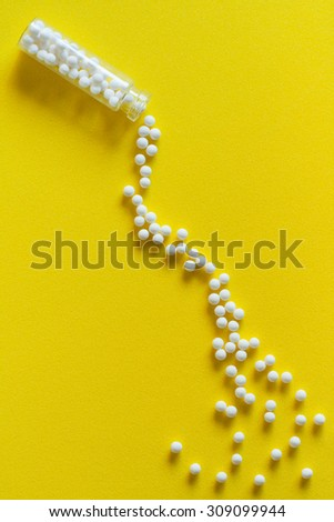 Homeopathic medicine spillage - Overhead view of homeopathic pills (made from inert substance - sugar/lactose) spillage effect from a bottle on a yellow surface. Natural light used. - stock photo