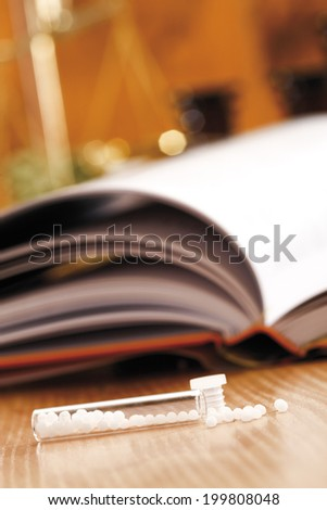 Homeopathic remedy in front of homeopathic book, close-up - stock photo