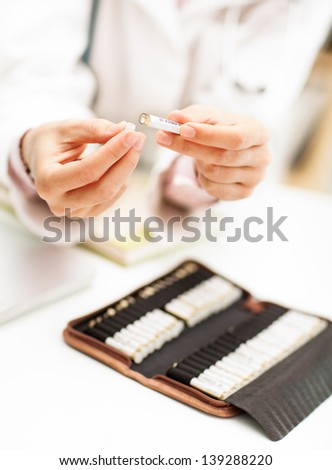 Homeopathist with a selection of homeopathic pills.
