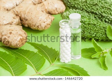 Homeopathy - A concept with homeopathic medicine (sugar/lactose pills and liquid homeopathic substance) pictured along with homeopathic vegetables and herbs (ginger, bitter gourd, neem, basil). - stock photo