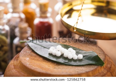 Homeopathy pills on the green leaf closeup - stock photo