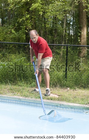 homeowner swimming pool maintenance man cleaning swimming pool skimming debris from water