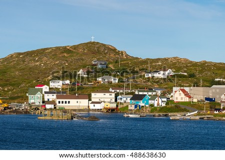 Homes on a rocky hill with a white cross in Twillingate, Newfoundland