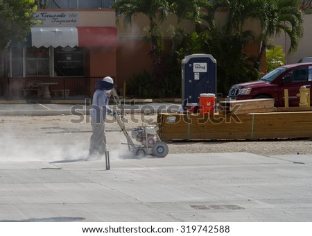 Homestead, FLORIDA - August 04, 2015: Construction worker working with a circular saw cutting stones and marble on a commercial construction site downtown Homestead, Florida - stock photo
