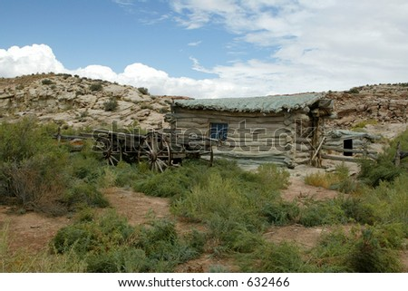 homestead in the desert log cabin and wagon - stock photo