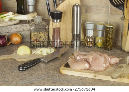 Homework chicken meat, slicing chicken breast fillet, kitchen table with ingredients for cooking