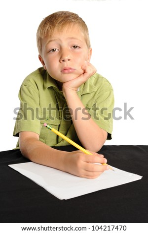 Homework is Boring. Seven year old boy sitting at a table not interested in doing his homework. - stock photo