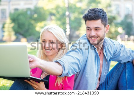 Homework. Student girl and boy student hold a laptop and looking at the camera while sitting on the grass near the building of the university on a break. man points a finger at laptop - stock photo