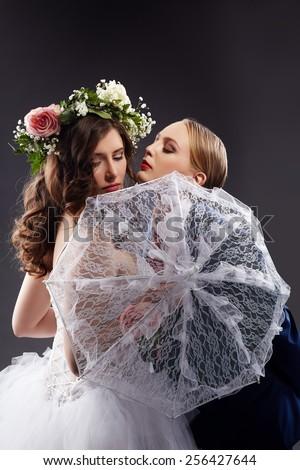 Homosexual girlfriends posing in wedding costumes - stock photo
