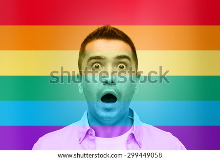 homosexual, homophobia, intolerance, emotions and people concept - shocked gay man shouting over rainbow flag background - stock photo