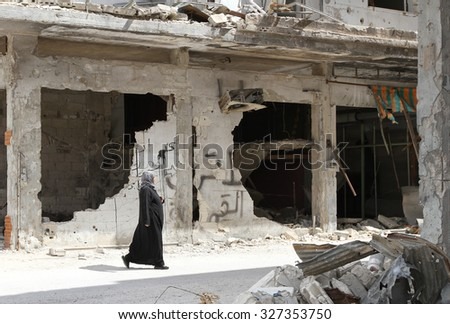Homs, Syria, September 2013 A woman walks near a house in the city of Homs destroyed in the fighting between the rebels of the Syrian National Army - stock photo
