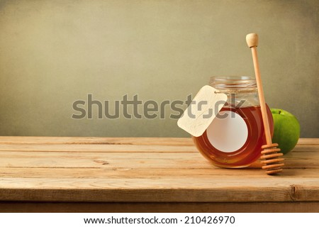 Honey and apple on wooden table with copy space - stock photo