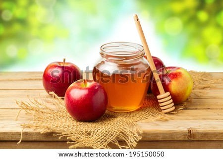 Honey and apples on wooden table over bokeh background - stock photo