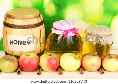 Honey and apples with cinnamon on wooden table on natural background