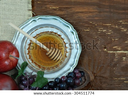 Honey and apples with grapes signifying wine are symbols of the Jewish holiday, Rosh Hashana. Perspective is from overhead. Copy space on right side. Rustic elements including burlap and old pewter.